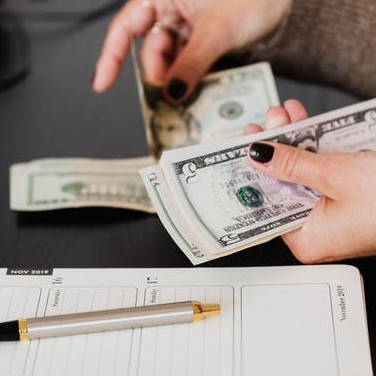 image of an individual counting money with a pen and paper on the table-How To Earn Money Online  While Still Learning