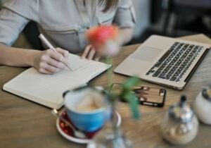 image of lady with pen , paper and a laptop